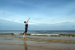 赤足走在海滩跳跃的和哺养的白顾的妇女 免版税库存图片