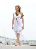 赤足走在白色礼服的妇女户外 免版税图库摄影