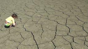 赤足走的孩子在破裂的干燥地面 股票视频