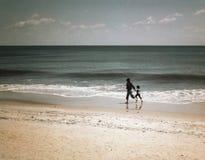 赤足跑在海滩的妇女和孩子 免版税库存图片