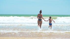 赤足跑在湿沙子,背面图的幸福家庭妈妈和婴孩 r 影视素材