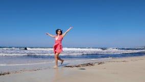 赤足跑沿沙滩的年轻白种人妇女和投掷她的在天空的帽子 她戴红色礼服和太阳镜与 股票录像