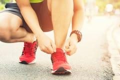 ?? 赤足跑鞋关闭  坐男性的运动员栓跑步的鞋带 免版税库存图片
