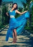 赤足跳舞在一件长的蓝色礼服的美丽的妇女 免版税库存图片