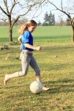 赤足踢橄榄球的小女孩 免版税库存照片