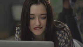 赤足说谎在床上和看膝上型计算机的美丽的女孩 影视素材