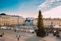 赫尔辛基,芬兰 走在圣诞节与圣诞树的Xmas市场上的人们在参议院正方形在背景中  库存照片