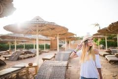走一个热带海滩假日的妇女 豪华木休息室和晴朗的户外背景 库存照片