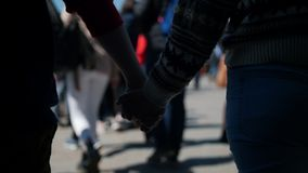 走一对年轻的夫妇握手在人群附近 股票视频
