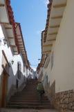 走上升在楼梯的背包徒步旅行者在库斯科,秘鲁 免版税库存照片