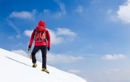 走上升沿一个多雪的倾斜的登山家。 免版税库存照片