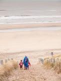 走下来到海滩的妇女和两个小孩子 免版税库存照片