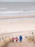 走下来到海滩的妇女和两个小孩子 库存图片