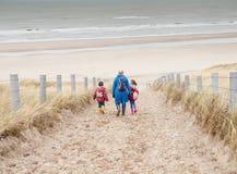 走下来到海滩的妇女和两个小孩子 库存照片