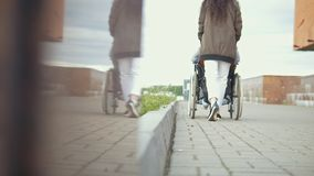 走与一个轮椅的残疾人的少妇在街道下 股票录像