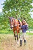 走与一匹马的女孩在庭院里 免版税图库摄影