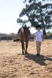 走与一匹马的车手女孩在大农场 库存图片