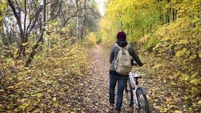 走与一辆自行车的年轻女人在秋天森林里 股票录像