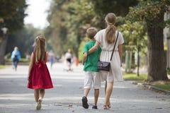 走与两个孩子、小女儿和儿子的后面观点的年轻白肤金发的长发妇女沿晴朗的公园胡同在弄脏 免版税库存图片