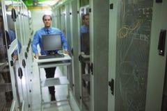 走与个人计算机的技术员在走廊 库存图片