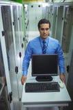 走与个人计算机的技术员在走廊 库存照片