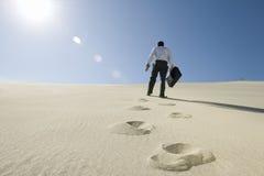 走与公文包的商人在沙漠 库存图片