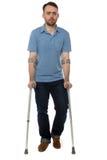 走与前臂拐杖的年轻残疾人 免版税库存照片