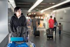 走与台车的年轻亚裔人在机场终端 免版税库存照片