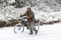 走与在一个多雪的风景的自行车的未知的人在northe 免版税库存图片
