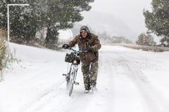 走与在一个多雪的风景的自行车的未知的人在northe 免版税图库摄影