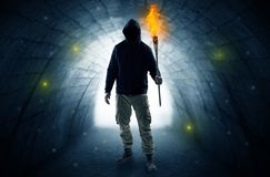 走与在一个黑暗的隧道的燃烧的大烛台的人 免版税库存照片