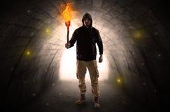 走与在一个黑暗的隧道的燃烧的大烛台的人 库存图片