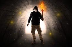 走与在一个黑暗的隧道的燃烧的大烛台的人 免版税库存图片