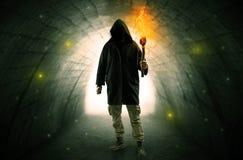 走与在一个黑暗的隧道的燃烧的大烛台的人 免版税图库摄影