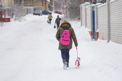 走与在一条多雪的街道上的小狗的女小学生 免版税库存照片