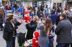 走与在圣诞节市场上的小圣诞老人的年轻母亲 图库摄影