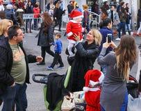 走与在圣诞节市场上的小圣诞老人的年轻母亲 库存照片