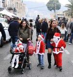 走与在圣诞节市场上的小圣诞老人的年轻母亲 库存图片