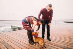 走与在多雨停泊处的狗的年轻愉快的夫妇在秋天 背景峡湾光芒海运星期日 库存图片