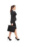 走与在她的现有量的一个公文包的女实业家 免版税库存图片