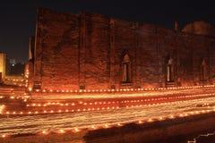 走与在手中被点燃的蜡烛在寺庙附近 库存图片