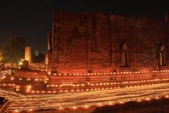 走与在手中被点燃的蜡烛在寺庙附近 免版税库存照片