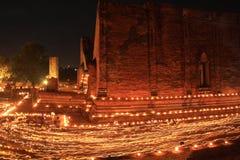 走与在手中被点燃的蜡烛在寺庙附近 免版税库存图片