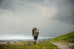 走与在海岸的一个远足的背包的背面图年轻人 免版税库存图片
