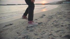 走与在海滩的西伯利亚爱斯基摩人狗的年轻美丽的女性在日落,慢动作 股票视频