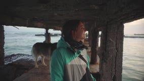 走与在海滩的西伯利亚爱斯基摩人狗的年轻美丽的女性在日落,慢动作 影视素材