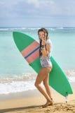 走与在海滩的冲浪板的冲浪者女孩 库存图片