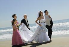 走与在海滩的家庭的新娘和新郎 免版税库存照片