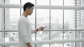 走与在窗口背景的一个电话的亚洲男性中间被射击的外形 影视素材