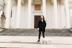 走与在街道上的一条狗的妇女 库存照片